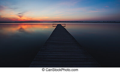 Old empty wooden jetty on lake, during sunrise.