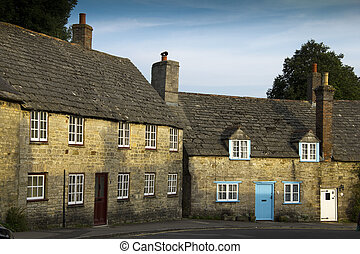 Early evening sunshine plays across the beautiful old buildings of Corfe in Dorset