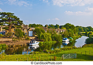 Old English village with river with boats, houses