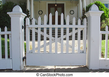 White picket entry gate in front of a early 1900's home. Pro-mist filter gives a slight glowing nostalgic quality to the image.