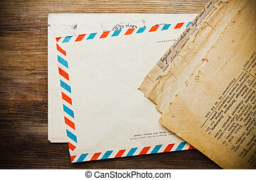 Old envelope with aged newspaper on wooden background