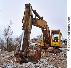 Old excavator on the ruins of an old house.