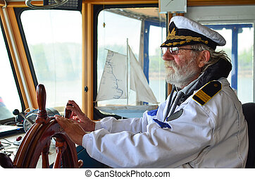 Ship navigation, experienced captain, old sea dog with grey hair and beard on his working place, ship navigation cabine