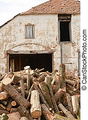 Old facade of a building ruined with stack of trunk tree near her
