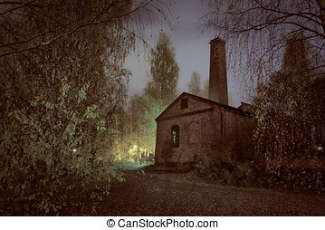 Old factory ruins in the middle of the spooky forest at...