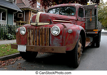 An old red farm truck parked in front of some retro homes.