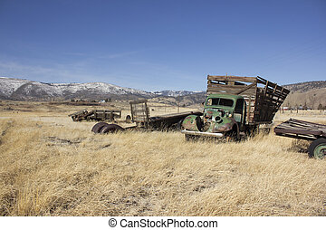 Old farm truck in a field of junk