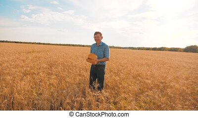 old farmer lifestyle man baker holds a golden bread and loaf in wheat field against the blue sky. slow motion video. successful agriculturist in field of wheat. harvest time. baker bread baking vintage agriculture concept
