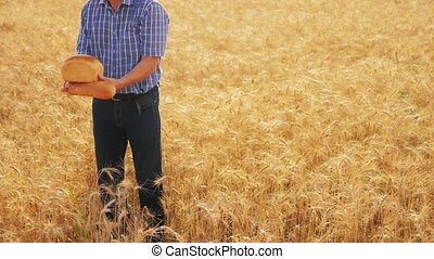 old farmer man baker holds a golden bread and loaf in ripe...