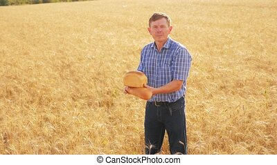 old farmer man baker holds a golden bread and loaf in ripe wheat field. lifestyle slow motion video. harvest time. old man baker bread baking vintage agriculture concept. successful agriculturist in field of wheat