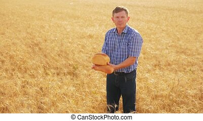 old farmer man baker holds a golden bread and loaf in ripe wheat field. slow motion video. harvest time. old man baker bread baking vintage agriculture concept. successful lifestyle agriculturist in field of wheat