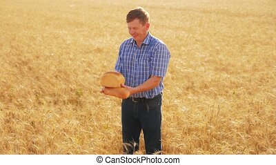 old farmer man baker holds a golden bread and loaf in ripe wheat field. slow motion video. harvest time. old man baker bread baking vintage agriculture concept. lifestyle successful agriculturist in field of wheat