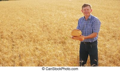 old farmer man baker holds a golden bread and loaf in ripe wheat field. slow motion video. harvest time. old lifestyle man baker bread baking vintage agriculture concept. successful agriculturist in field of wheat