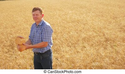 old farmer man baker holds a golden lifestyle bread and loaf in ripe wheat field. slow motion video. harvest time. old man baker bread baking vintage agriculture concept. successful agriculturist in field of wheat