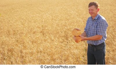 old farmer man baker holds a lifestyle golden bread and loaf in ripe wheat field. slow motion video. harvest time. old man baker bread baking vintage agriculture concept. successful agriculturist in field of wheat