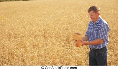 old farmer man baker lifestyle holds a golden bread and loaf in ripe wheat field. slow motion video. harvest time. old man baker bread baking vintage agriculture concept. successful agriculturist in field of wheat
