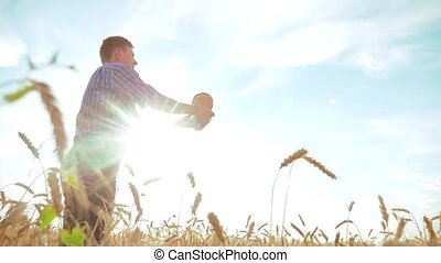 old farmer man baker silhouette holds a golden bread and...