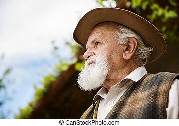 Old farmer with beard and hat standing by his farmhouse