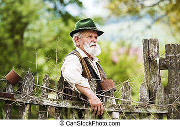 Old farmer with beard and hat standing by the lath fence ...