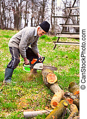 Old farmer with chainsaw cutting a tree