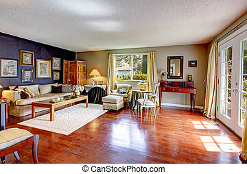 Big old living room with hardwood floor, couch, coffee table and antitque chest, chairs