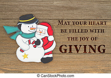 Old fashion Christmas giving greeting, A retro snowman and Santa Claus hugging on weathered wood background with text May your heart be filled with the joy of giving