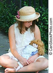 Adorable young teenager in straw hat holding her vintabe doll.