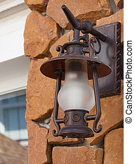 Old-fashion lamp hanging on sand stone wall