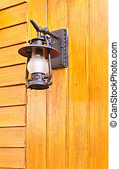 old-fashion lamp hanging on wooden wall