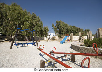 old fashioned children's playground in the greek islands with typical cyclades cubic architecture hotel in background