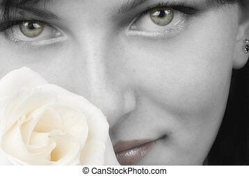 nice black and white portrait of a young woman with roses in her hands smelling and smiling with her fair eyes