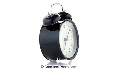 Old fashioned alarm clock ringing on white background.