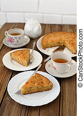 Old fashioned apple pie with black tea on wooden background