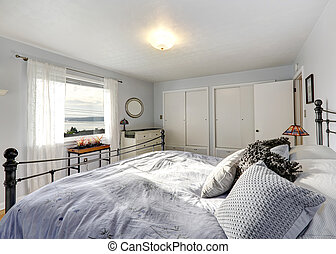 Old fashioned bedroom with iron frame bed