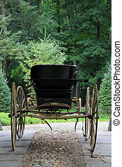 Old fashioned horse buggy on display with cobblestone and pebbles beneath it's big spoke wooden wheels.