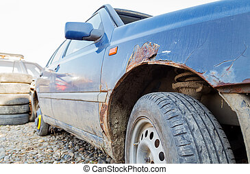 Side view of an old fashioned car in a junkyard