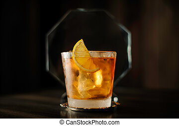 old fashioned cocktail with lemon on table