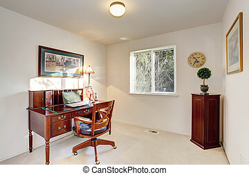 Old fashioned desk with drawers in home office interior.