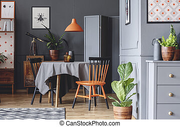 Old fashioned dining room interior with a table, chairs, orange lamp and plants