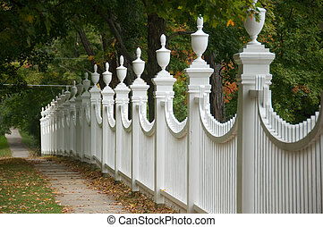 Old-fashioned fence - Old white picket fence in an autumn...
