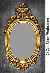 Old-fashioned oval gilt frame for a mirror on a gray concrete wall
