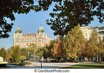 Beautiful autumn landscape with old fashioned historical building and square before on a background of clear blue sky in Budapest, Hungary.