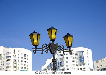 old-fashioned lantern on a background modern buildings of city