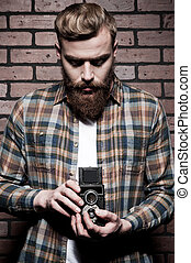 Old-fashioned photographer. Handsome young bearded man holding hands in pockets and looking at camera while standing against grey background