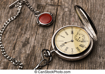 Old fashioned pocket watch with chain on rough wood