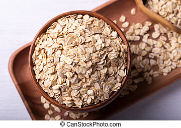 Old fashioned rolled oats in a wooden bowl on white wooden ...