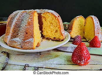 Old fashioned sand cake with cup of black tea and pieces of vanilla on wooden background. Egg-yolk sponge cake with stawberries on rustic white background..
