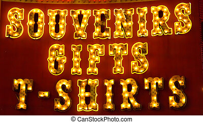 An old fashioned lit sign at a souvenir and T-Shirt store