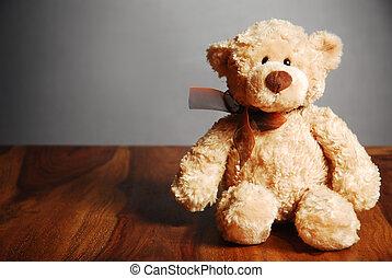 Old fashioned teddy bear on table, dark background