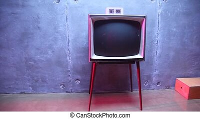 old-fashioned TV and hours on it stand about block wall